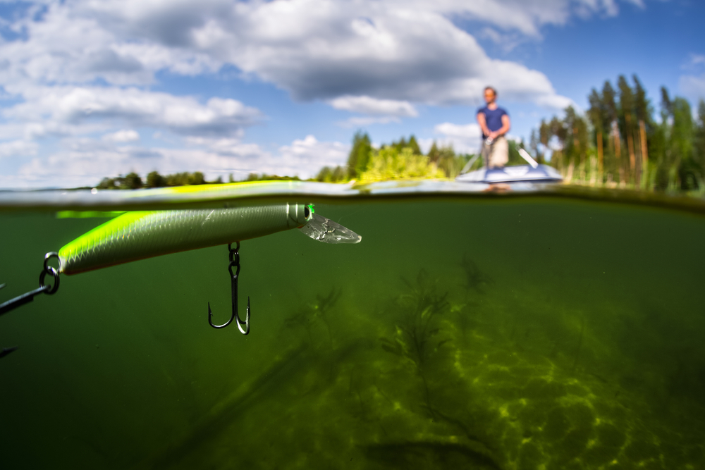 Split shot of the man fishing from the boat on the lake. Underwater view of the lake. Focus on the bait