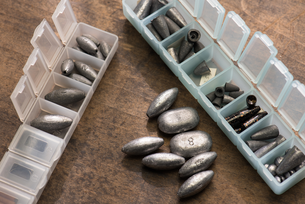 Lead weights or sinkers used for fishing, in variety of sizes, in a plastic separated compartment case.