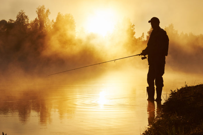 fisher fishing on foggy sunrise